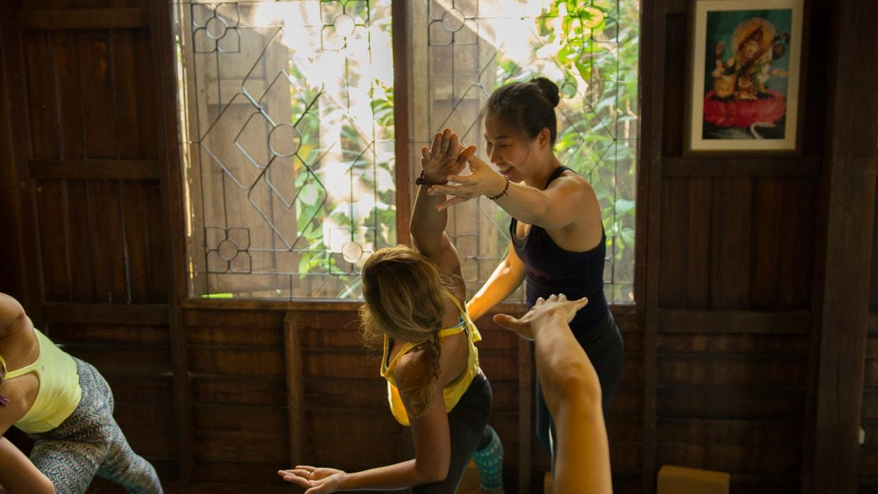 Kru Thom, who teaches the Hatha Yoga Class on Wednesday mornings at Wild Rose Yoga Studio Chiang Mai Thailand providing a yoga adjustment during her Hatha Yoga Class.